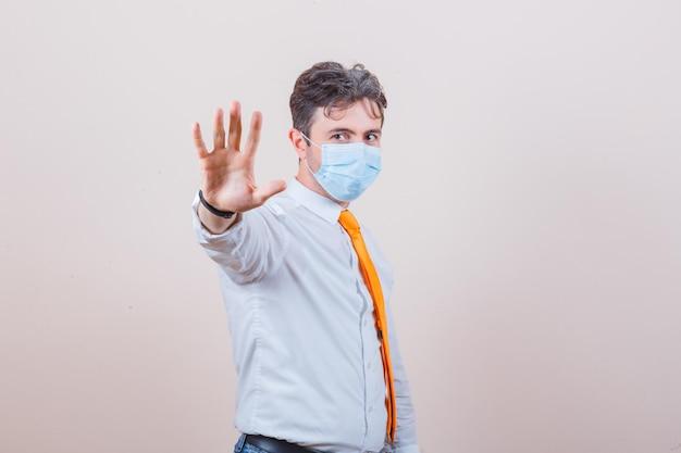 Junger mann in hemd, krawatte, maske mit stopp-geste und ernstem blick
