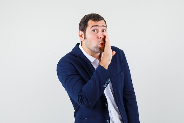 Junger mann in hemd und jacke, der geheimnis hinter hand erzählt und vorsichtig schaut