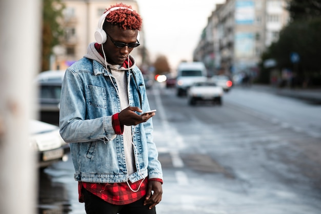 Junger mann in hörender musik des stadtmodells