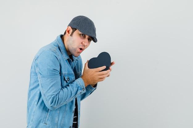 Junger mann in jacke, kappe, die geschenkbox schüttelt und aufgeregten raum für text sucht