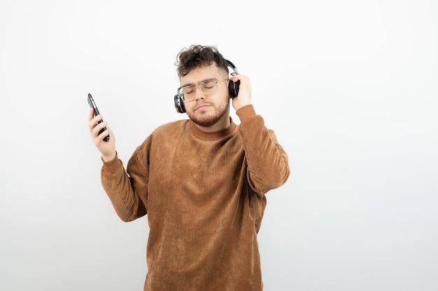 Junger mann in kopfhörern, der lieder auf seinem handy auswählt.
