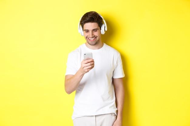Junger mann in kopfhörern, die nachricht auf smartphone lesen, lächeln, musik in kopfhörern hören und lied in app auswählen, über gelber wand stehen