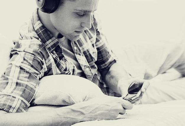 Junger mann in kopfhörern mit entspannendem zuhause des handys. einfarbig.