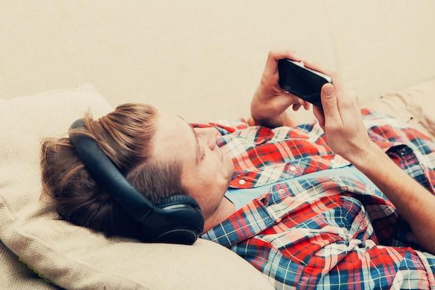 Junger mann in kopfhörern mit entspannendem zuhause des handys