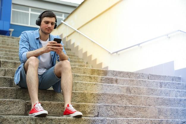 Junger mann in kopfhörern sitzt auf den stufen und schaut ins telefon