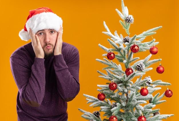 Junger mann in lila pullover und weihnachtsmütze, die kamera verwirrt und sehr besorgt neben weihnachtsbaum über orange hintergrund betrachten