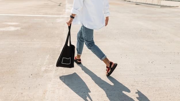 Junger mann in modischer sommerkleidung in stilvollen roten sandalen mit einer schwarzen vintage-tasche läuft die straße hinunter.