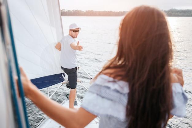 Junger mann in mütze und brille steht am bug der yacht und greift mit der hand nach brünette. er sieht sie an. sie steht auf und sieht ihn an. modell hält am rohr.