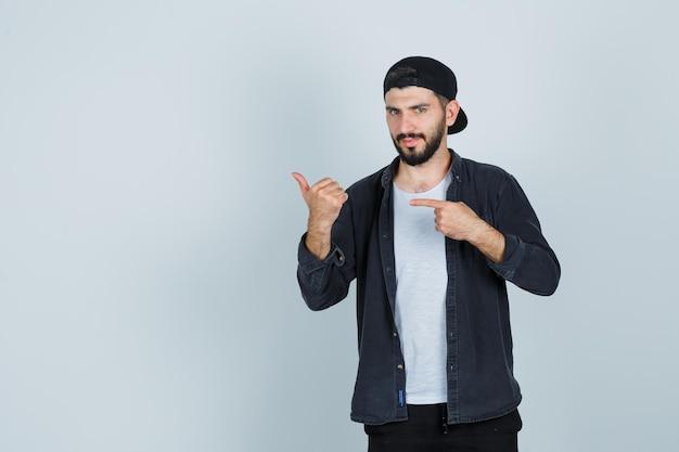 Junger mann in mütze zeigt mit dem finger und zeigt daumen nach oben