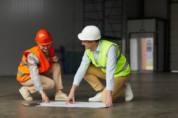 Junger mann in reflektierender kleidung bespricht projekt des neuen gebäudes zusammen mit seinem kollegen, während sie in leerem gebäude sind