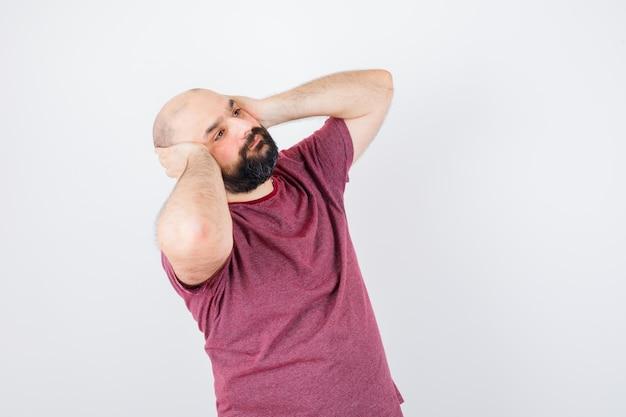 Junger mann in rosa t-shirt, der hände an den ohren hält, während er nach oben schaut und gelangweilt aussieht.