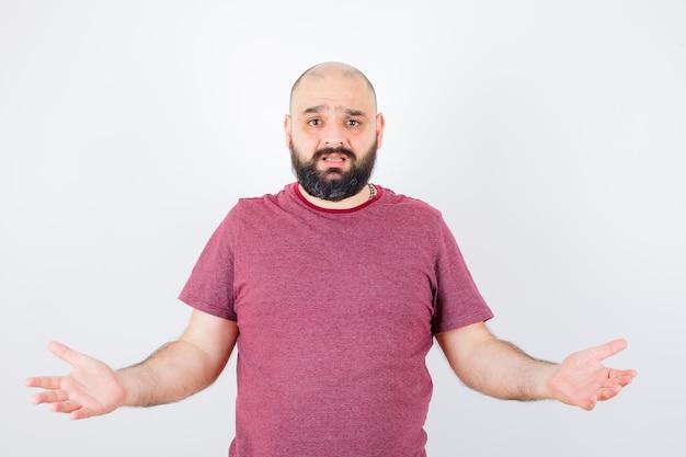 Junger mann in rosa t-shirt, der hilflose geste zeigt und unzufrieden aussieht, vorderansicht.