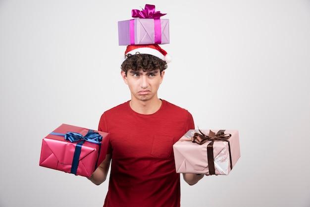 Junger mann in sankt-hut, der geschenke mit gelangweiltem ausdruck hält.