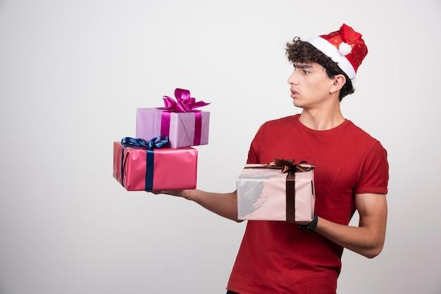 Junger mann in santa hut, der geschenke betrachtet.