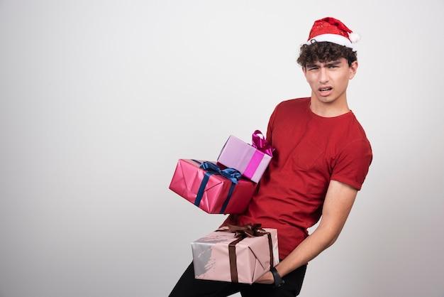 Junger mann in santa hut hält schwere geschenke.