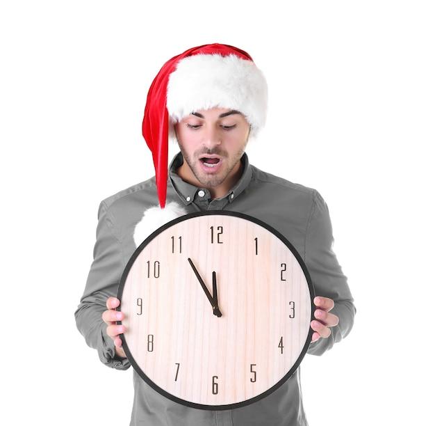 Junger mann in santa hut mit uhr auf weißer oberfläche. weihnachts-countdown-konzept
