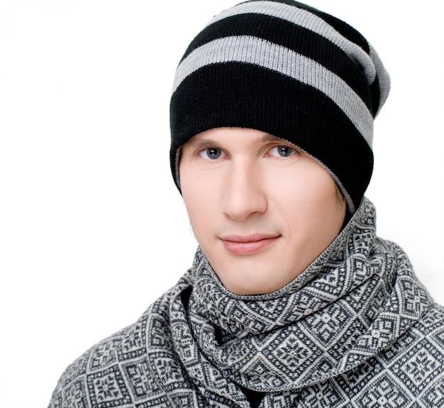 Junger mann in schal und mütze