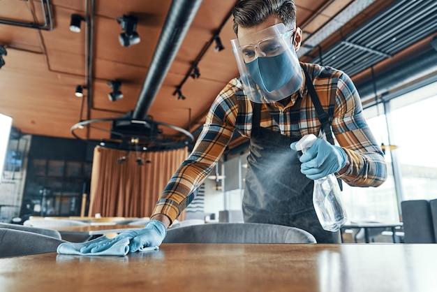 Junger mann in schützendem gesichtsschutz-reinigungstisch im restaurant