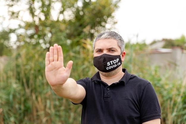 Junger mann in schützender gesichtsmaske. panik und isolation zu hause aufgrund des ausbruchs des coronavirus. mensch trägt eine maske, die seine hand mit ausgestreckter handfläche ausstreckt, um das covid-19-virus zu stoppen. coronavirus pandemie