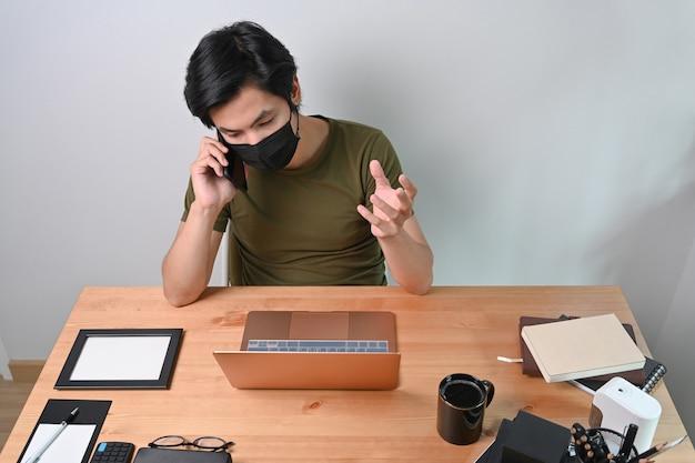 Junger mann in schutzmaske, der handy spricht und online mit laptop arbeitet.