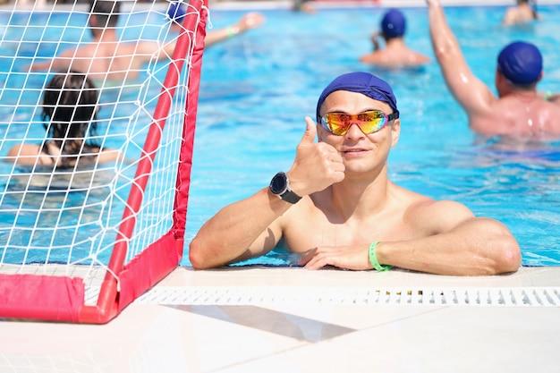 Junger mann in schwimmbrille und mütze zeigt daumen im pool