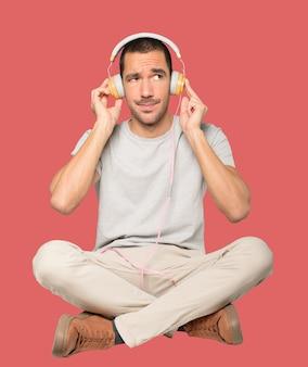 Junger mann in sitzender position mit einer zweifelnden geste Premium Fotos