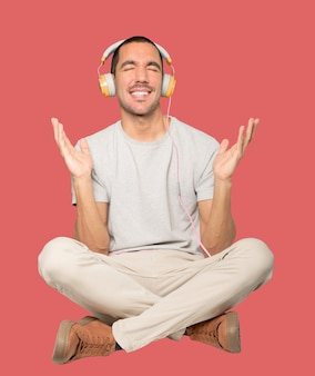 Junger mann in sitzender position mit einer zweifelnden geste