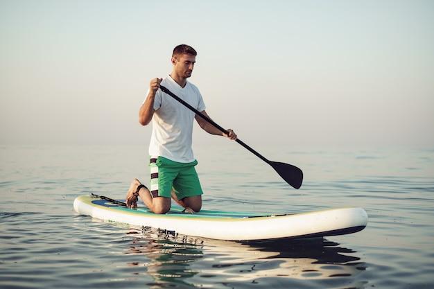 Junger mann in t-shirt und shorts schwimmt auf sup-board auf see