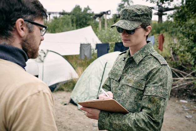 Junger mann in uniform, der das dokument in seinen händen betrachtet