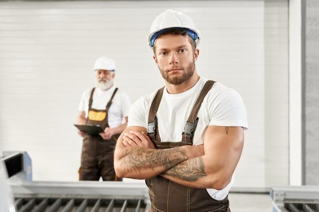 Junger mann in uniform und helm auf metallfabrik