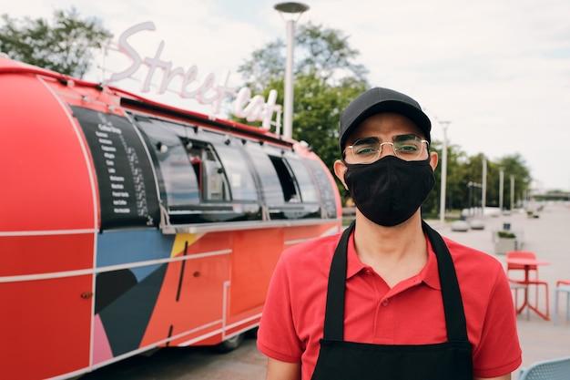 Junger mann in uniform und schwarzer maske mit blick in die kamera