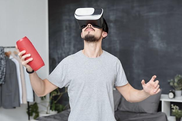Junger mann in vr-brille, die tragbaren lautsprecher hält, während virtuelle welt im videospiel erkundet