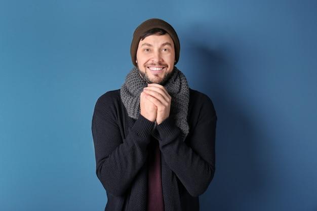 Junger mann in warmer kleidung auf farbigem hintergrund