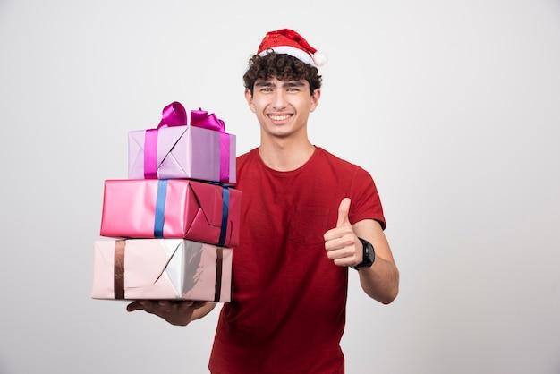 Junger mann in weihnachtsmütze, der daumen aufgibt.