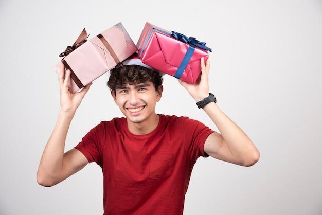Junger mann in weihnachtsmütze mit geschenken