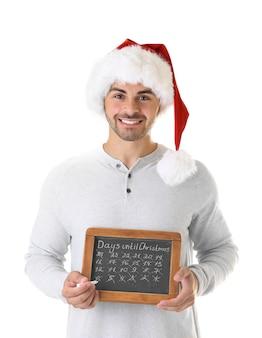 Junger mann in weihnachtsmütze mit tafel, die tage bis weihnachten zählt, auf weißem hintergrund