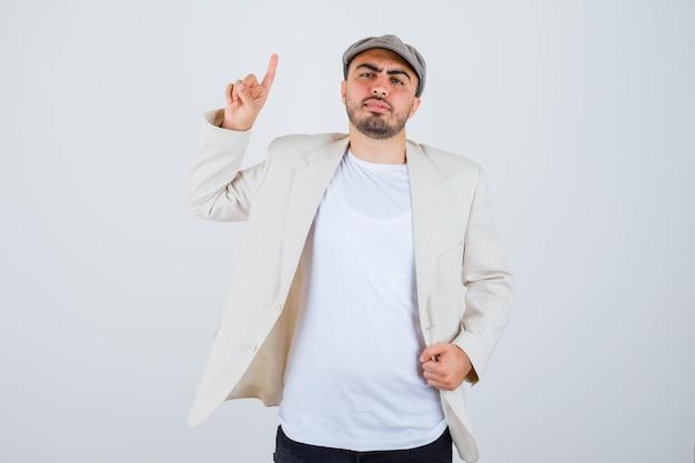 Junger mann in weißem t-shirt, jacke und grauer mütze, der den zeigefinger in der heureka-geste hebt und die hand auf der jacke hält und ernst aussieht