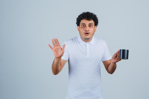 Junger mann in weißem t-shirt und jeans, der eine tasse tee hält, während er ein stoppschild zeigt und überrascht aussieht, vorderansicht.