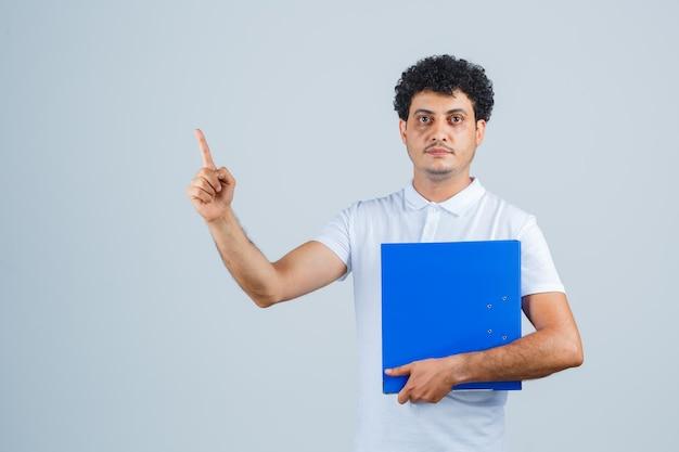 Junger mann in weißem t-shirt und jeans, der einen dateiordner hält, den zeigefinger in der heureka-geste hebt und vernünftig aussieht, vorderansicht.