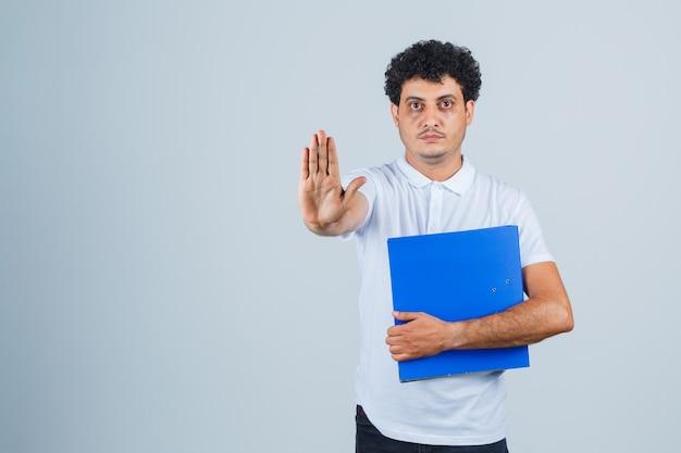 Junger mann in weißem t-shirt und jeans, der einen dateiordner hält und ein stoppschild zeigt und ernst aussieht, vorderansicht.
