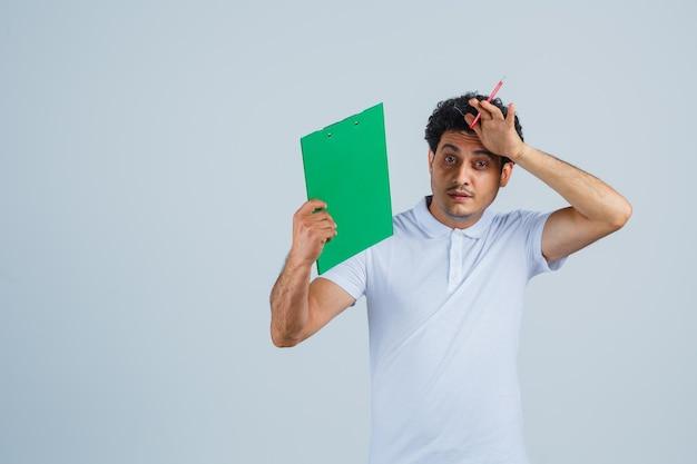 Junger mann in weißem t-shirt und jeans, der notizbuch und stift hält, die hand auf die stirn hält und gestresst aussieht, vorderansicht.