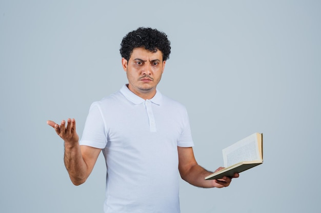 Junger mann in weißem t-shirt und jeans, der sich fragend die hand ausstreckt, während er ein buch hält und verwirrt aussieht, vorderansicht.
