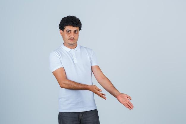 Junger mann in weißem t-shirt und jeans streckt sich die hände nach unten und sieht ernst aus, vorderansicht.