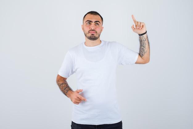 Junger mann in weißem t-shirt und schwarzer hose, der den zeigefinger in der heureka-geste hebt und nachdenklich aussieht