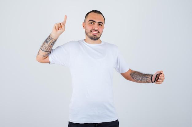Junger mann in weißem t-shirt und schwarzer hose, der etwas am telefon ansieht und den zeigefinger in der heureka-geste hebt und glücklich aussieht looking