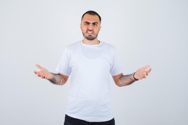 Junger mann in weißem t-shirt und schwarzer hose, der sich fragend die hände ausstreckt und verwirrt aussieht looking