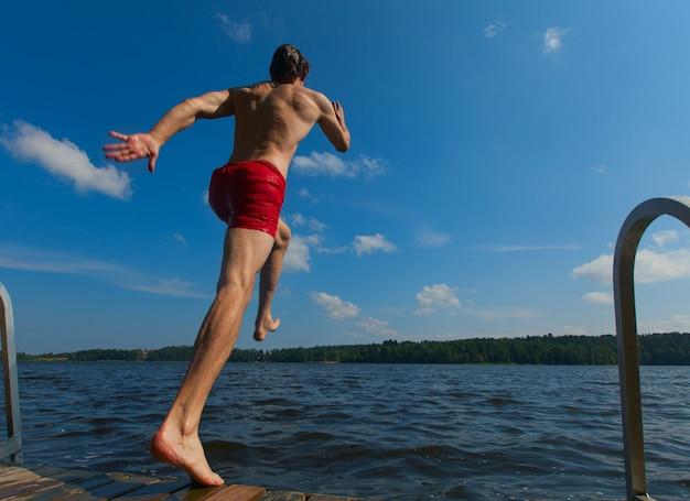 Junger mann ins wasser springen