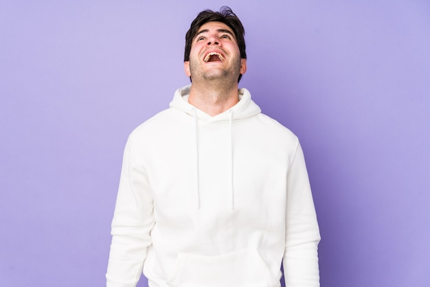 Junger mann isoliert auf lila raum, der sehr wütend, wutkonzept, frustriert schreit.