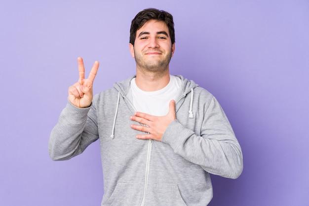 Junger mann isoliert auf purpur, der einen eid leistet und hand auf brust legt.