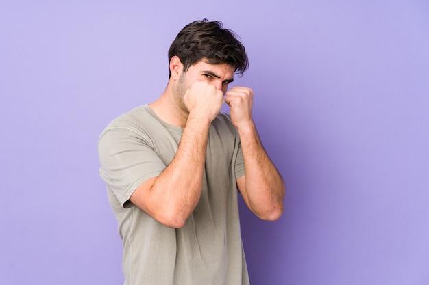 Junger mann isoliert auf purpur, der einen schlag, zorn wirft, wegen eines argumont kämpft, boxen.